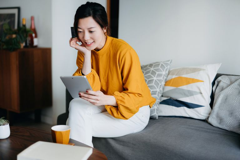Young Asian woman looking at a tablet.