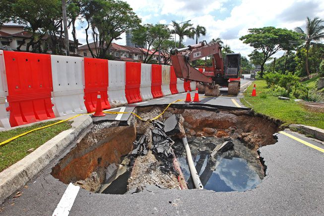 After a downpour, a giant sinkhole had swallowed traffic lights and cut off power in Kuala Lumpur