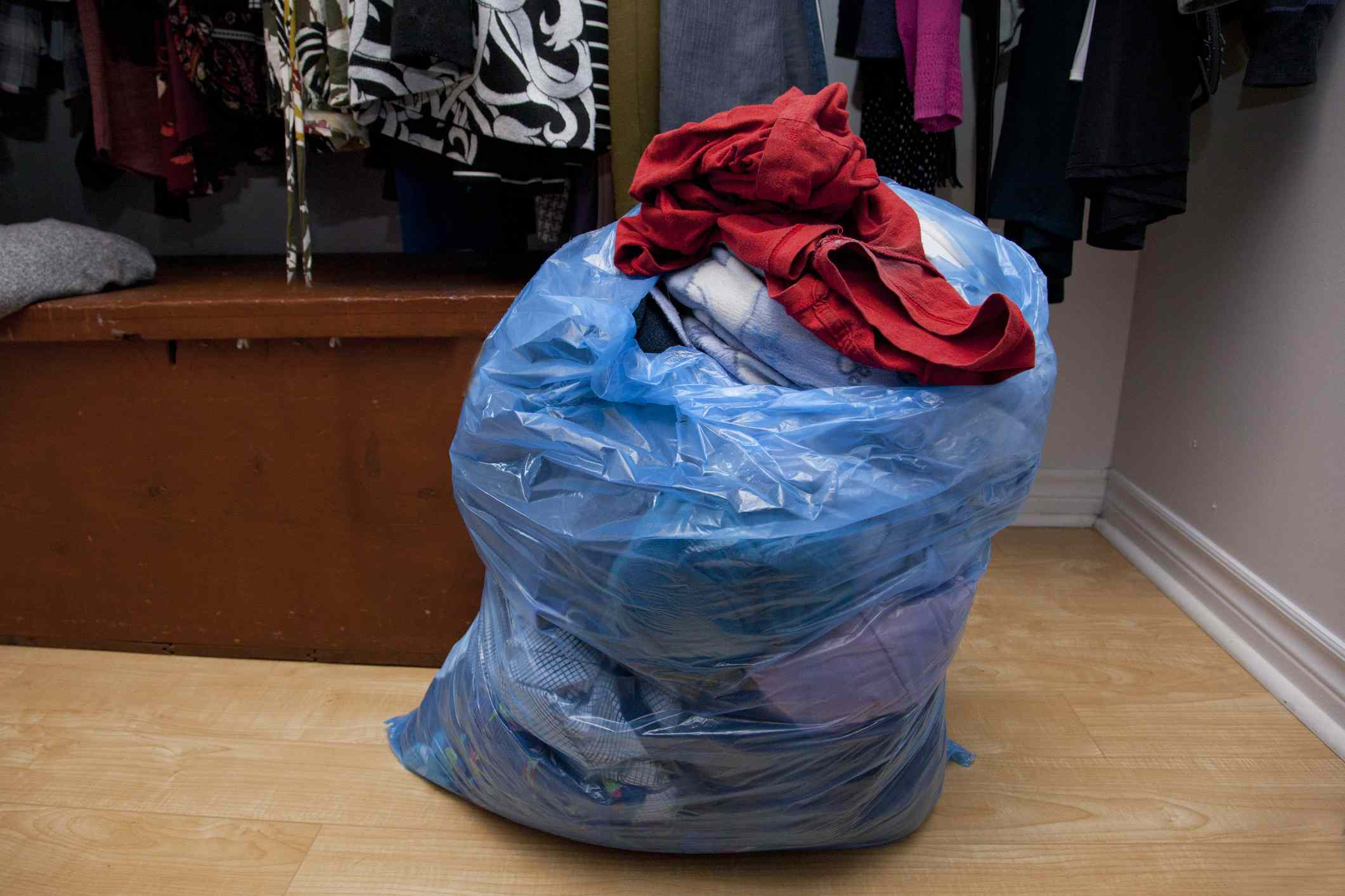 A plastic bag reused to hold clothes.