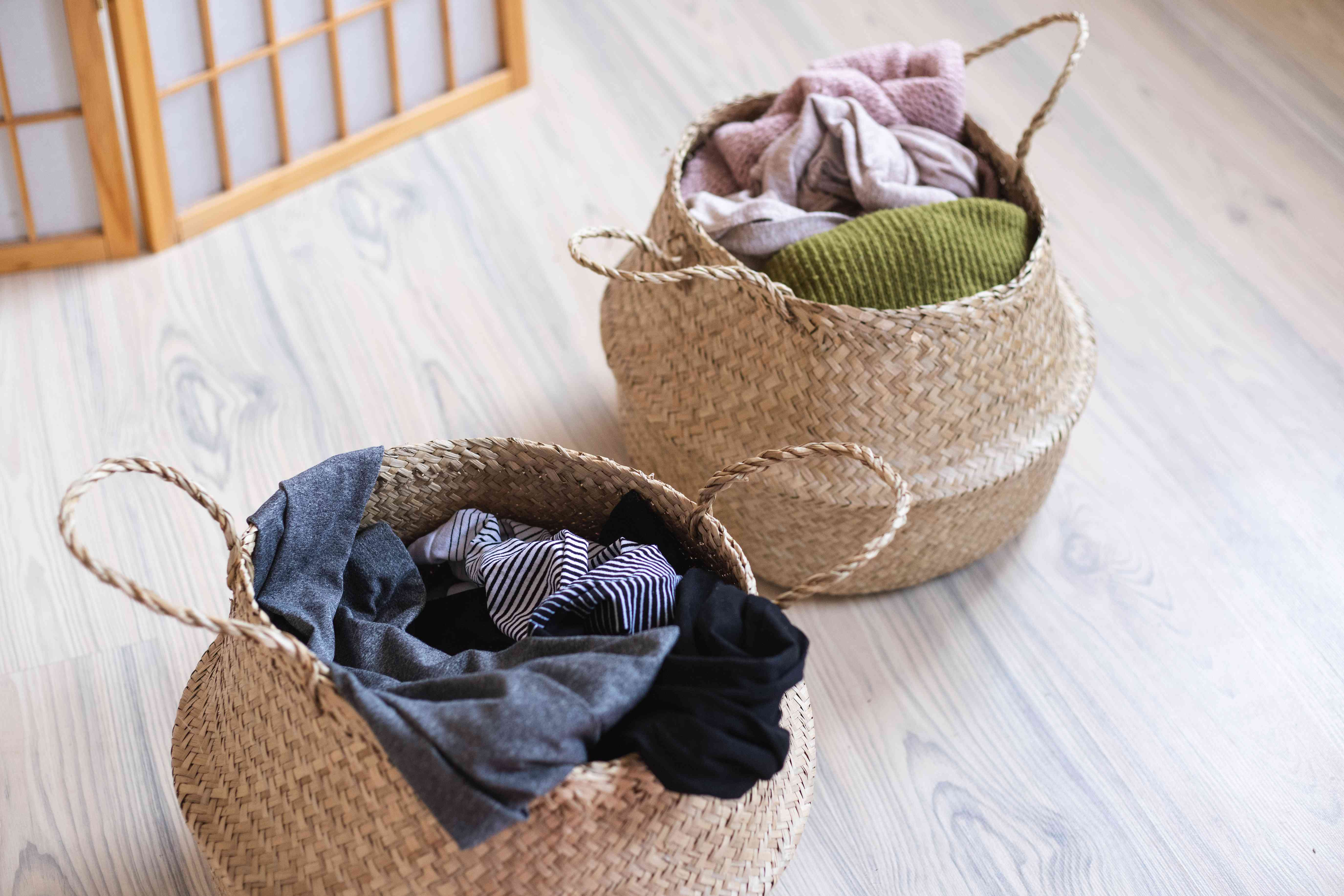 two woven basket laundry hampers, separated into knitwear and workout gear clothing