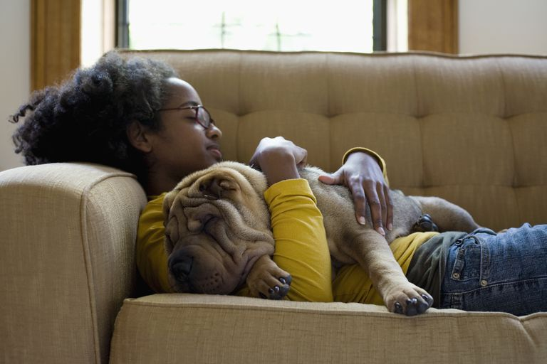 A young woman and her Shar-Pei napping on a couch