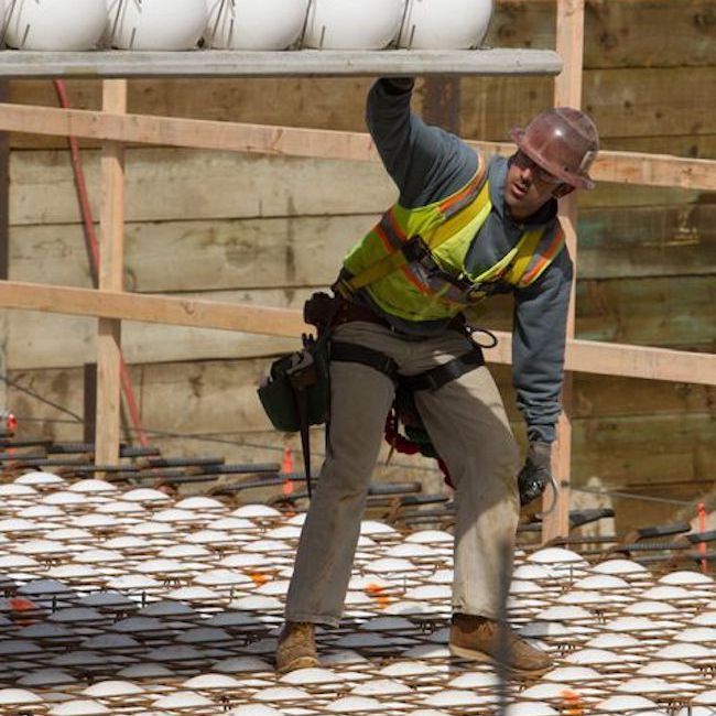 Construction worker guiding a piece of Bubbledeck into place