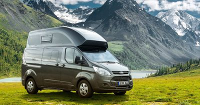 A gray van with a camper top, parked in from of a mountain vista