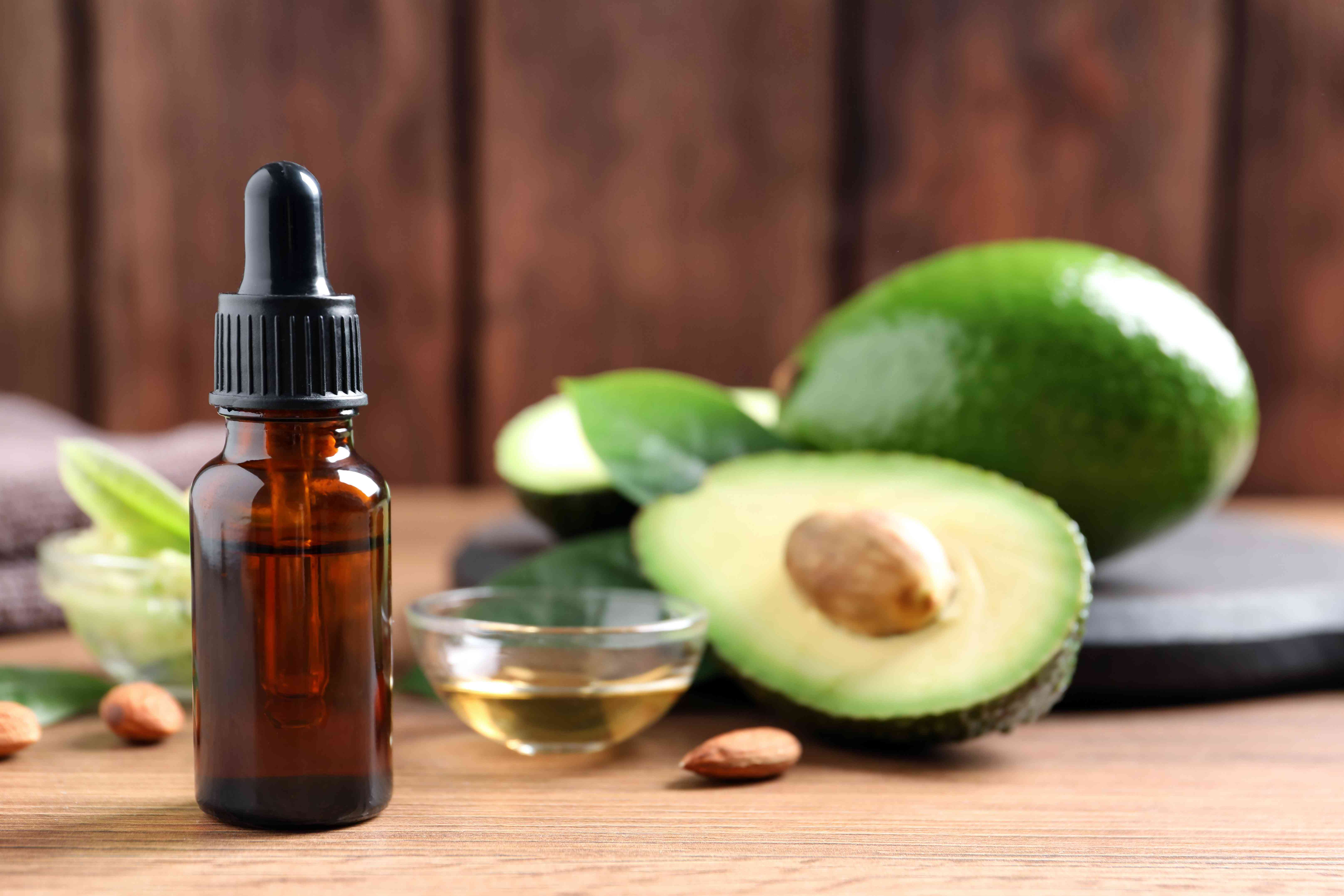 Bottle of essential oil, fresh avocado and almonds on wooden table, space for text