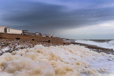 Foam creeps up a beach towards a town.
