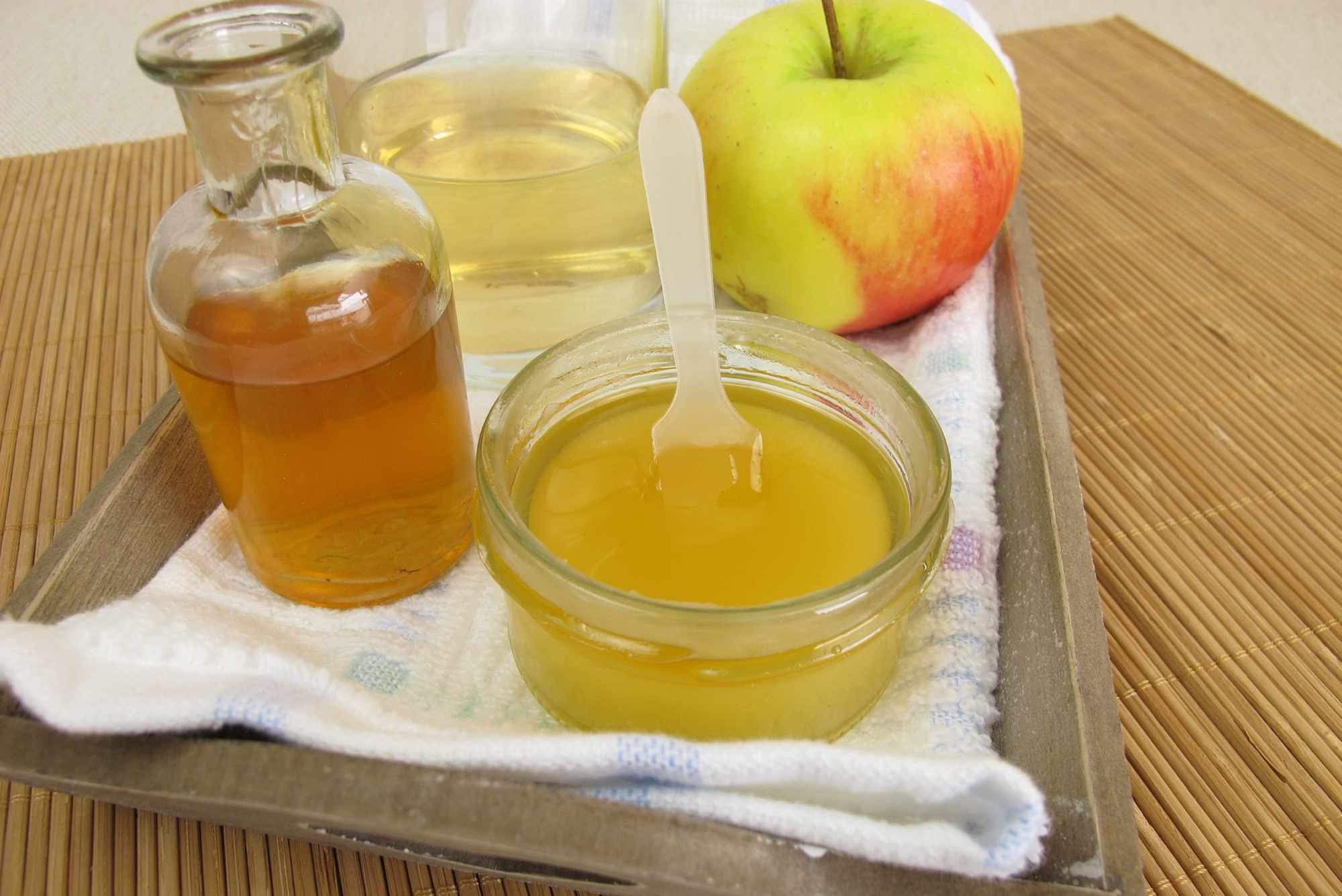 Apples and apple cider vinegar on a tray