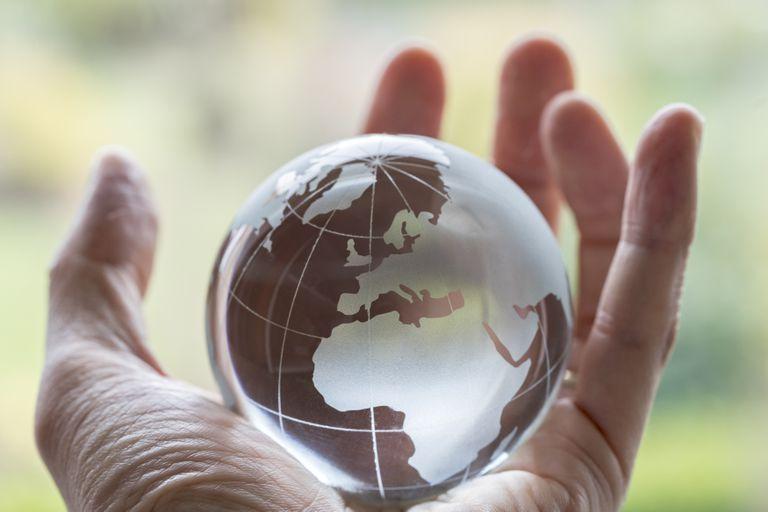 A human hand holding a globe