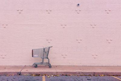 empty shopping car against pink brick wall