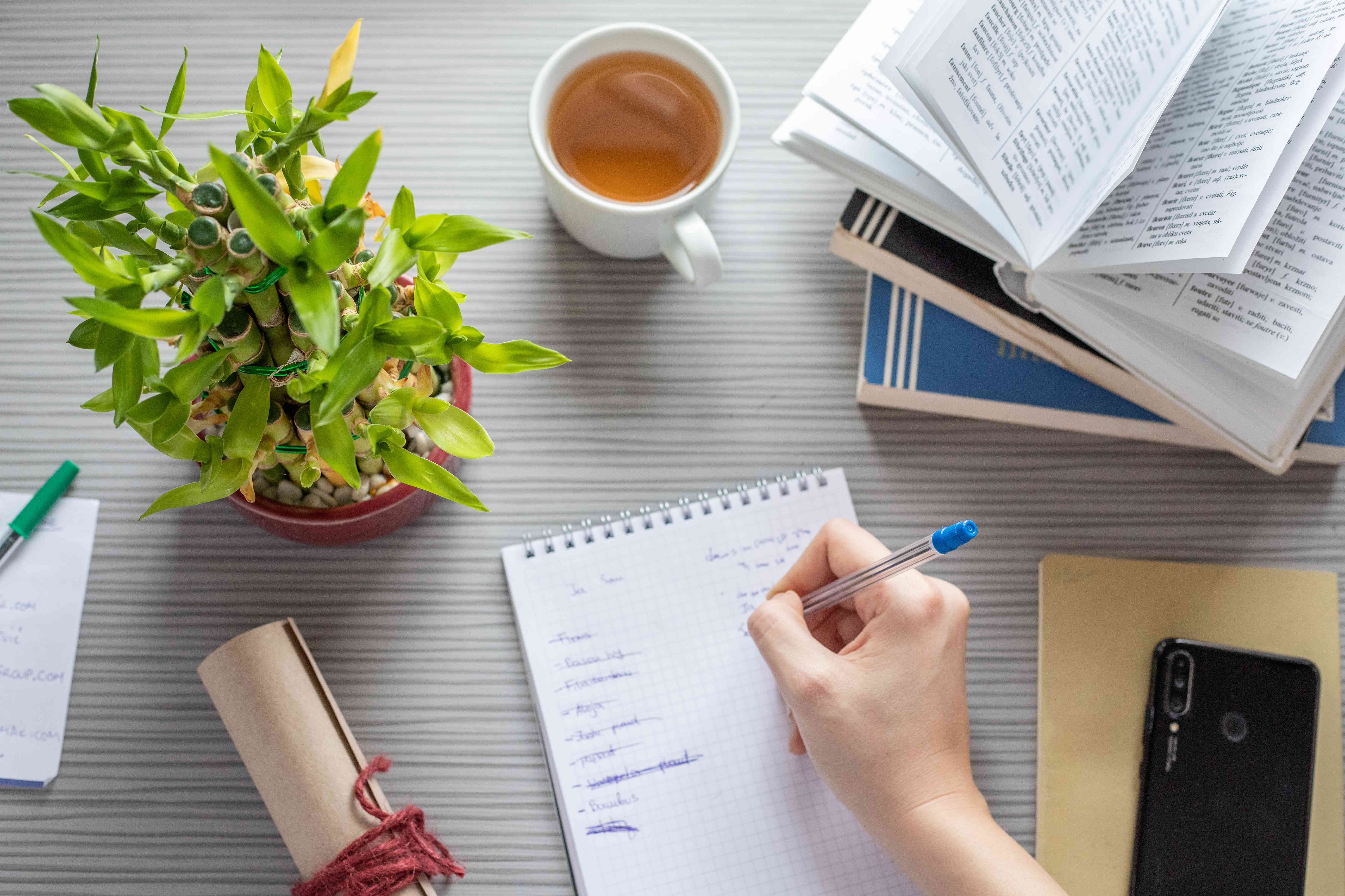 overhead shot of work desk while person writes notes next to lucky bamboo plant