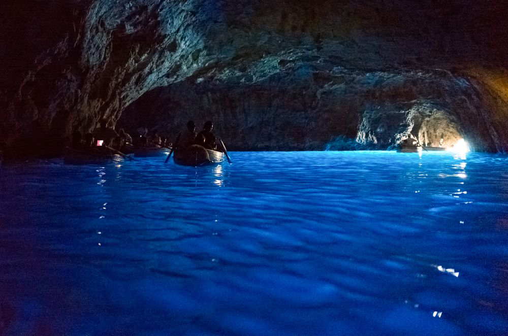 People paddle boats through a water cave, illuminated by sunlight