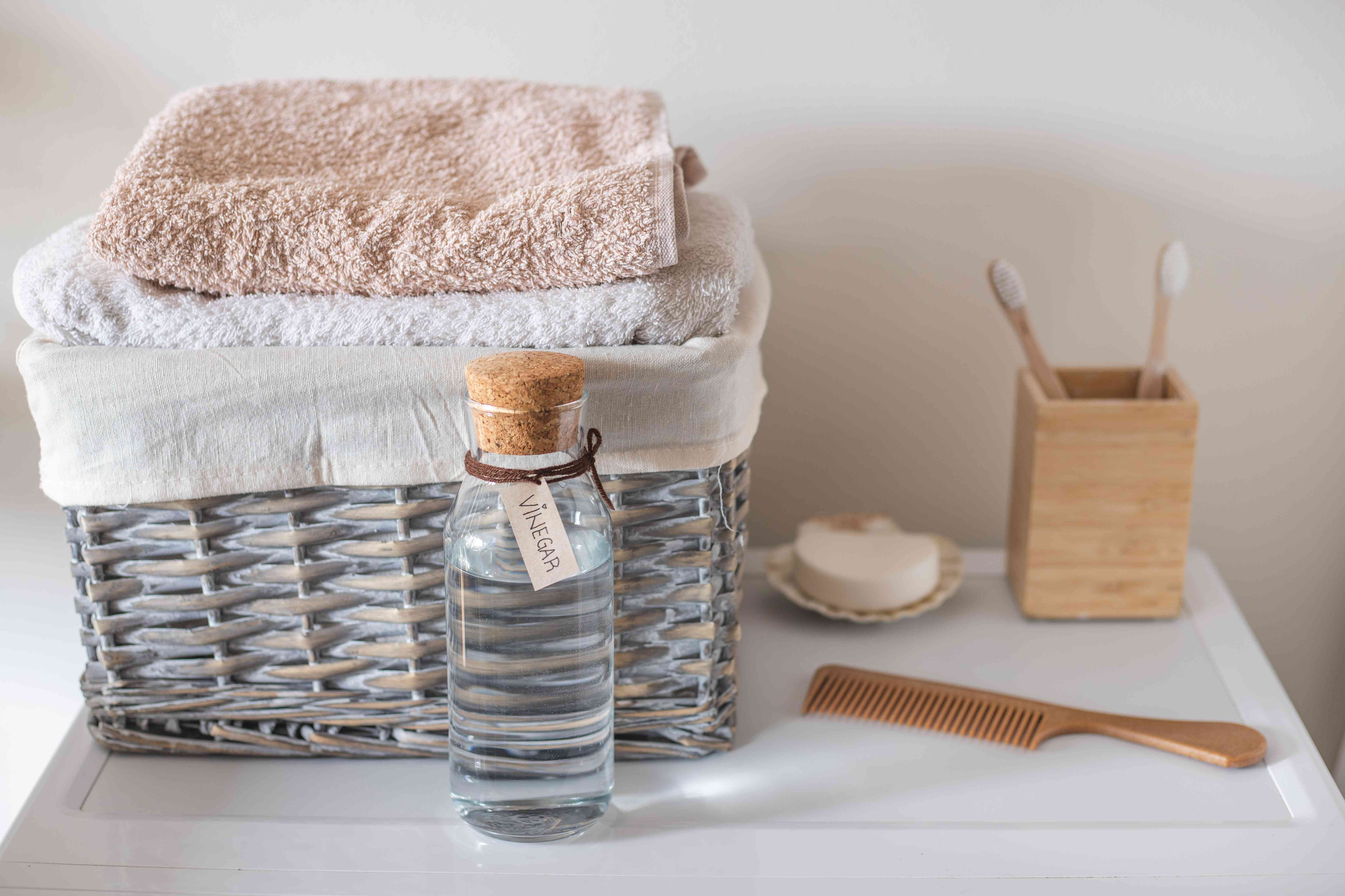 top of washing machine with glass bottle of white vinegar, laundry basket, comb, toothbrush