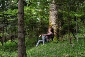 woman leans against tree deep in thought in heavily wooded forest
