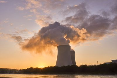 Steam clouds billowing into the sky coming from nuclear power plant at sunset