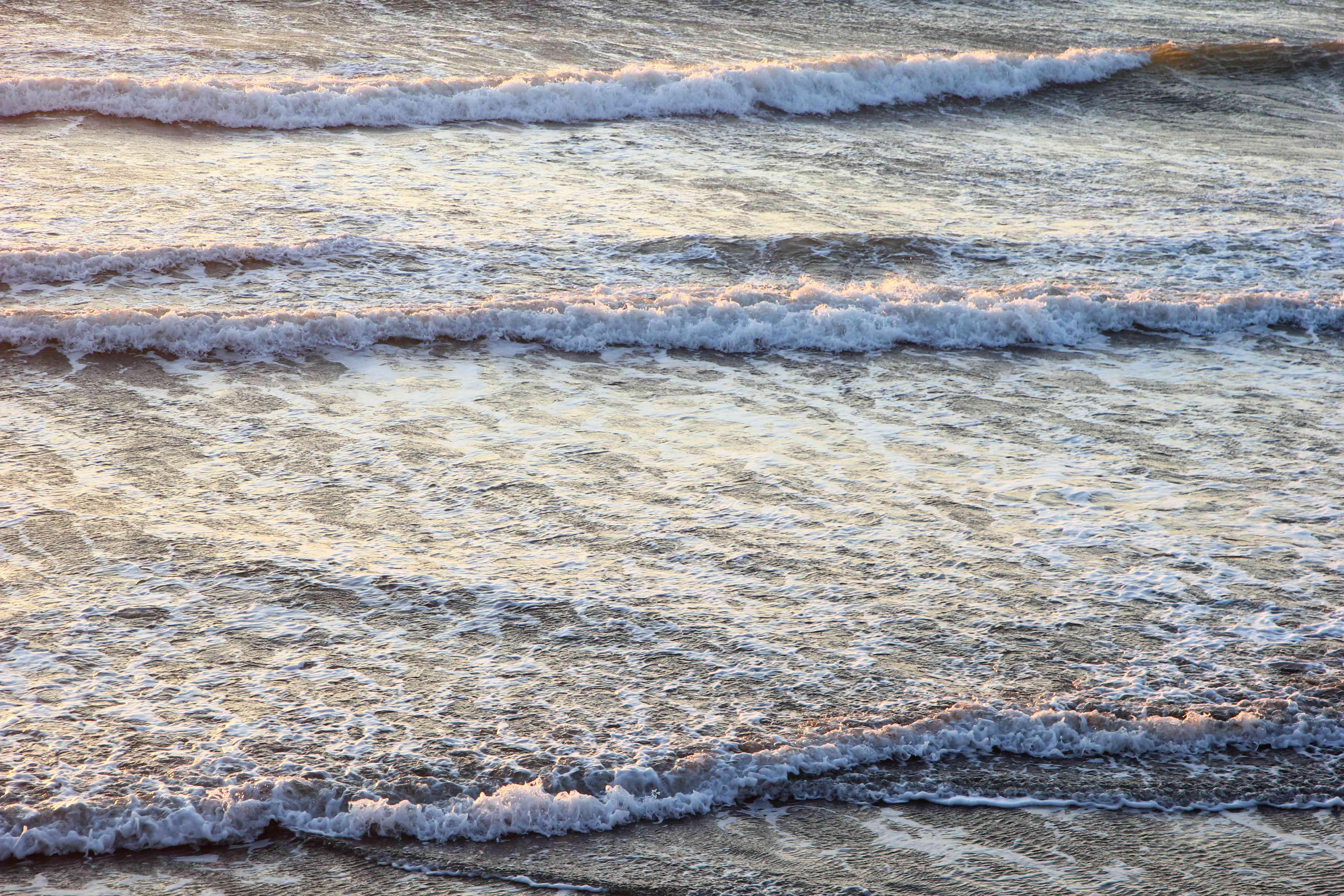 foamy waves roll upon ocean shore