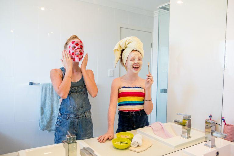pre-teen girls in front of bathroom mirror