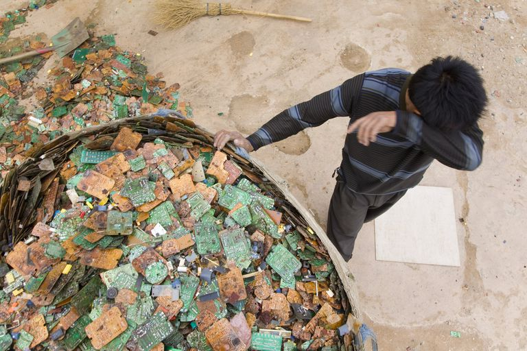 A man covers his face sorting through e-waste in China.