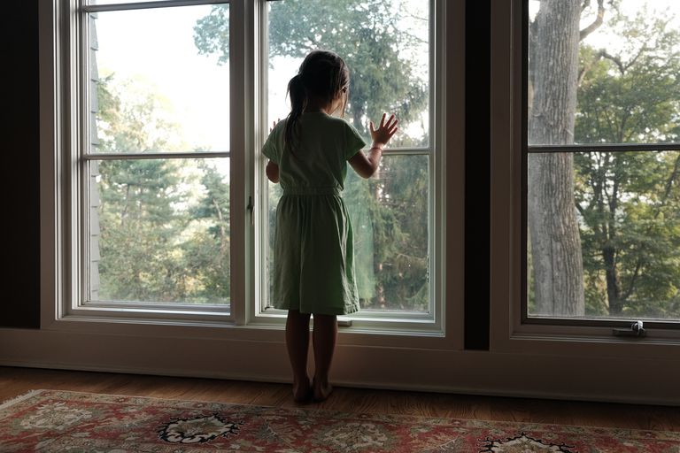 little girl looks out window to outside