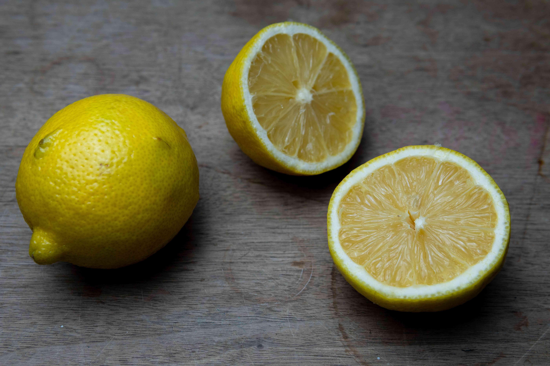 cut lemons on wooden cutting board