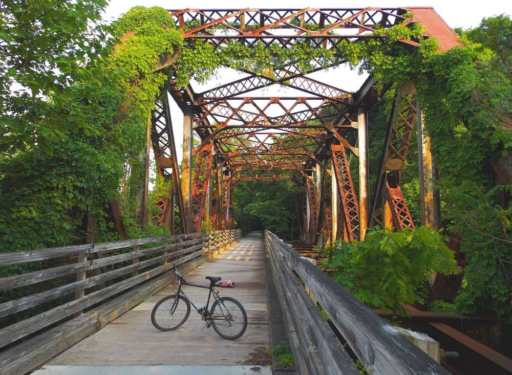 A bike sits on an old rail bridge with ivy climbing the trestles