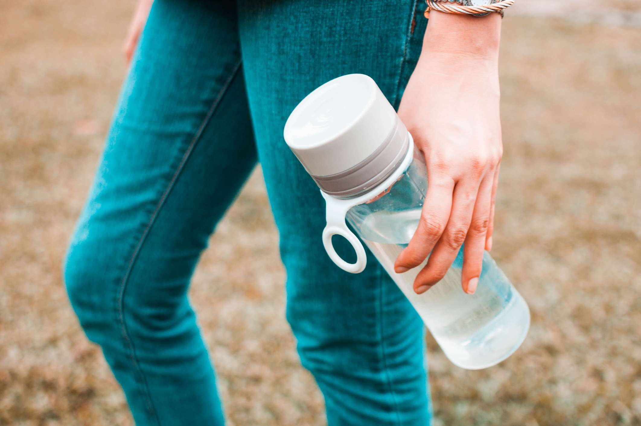 A woman holding a glass water bottle outside.