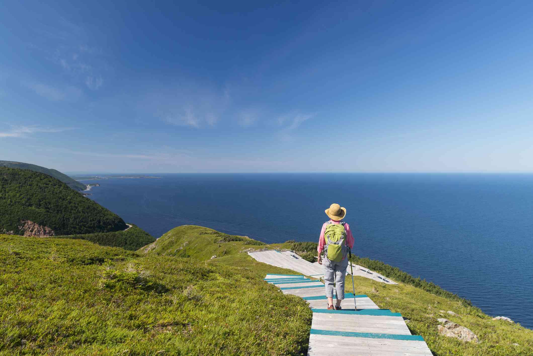 Hiker walking along Cabot Trail boardwalk overlooking water