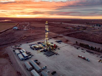 Drone View Of An Oil Or Gas Drill Fracking Rig As The Sun Sets In New Mexico