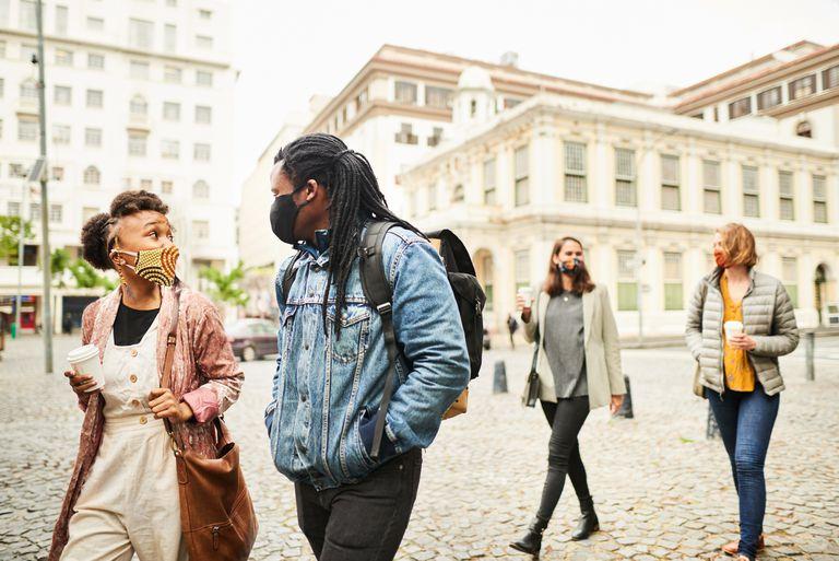 Two pairs of people walking down a cobblestone walkway wearing masks
