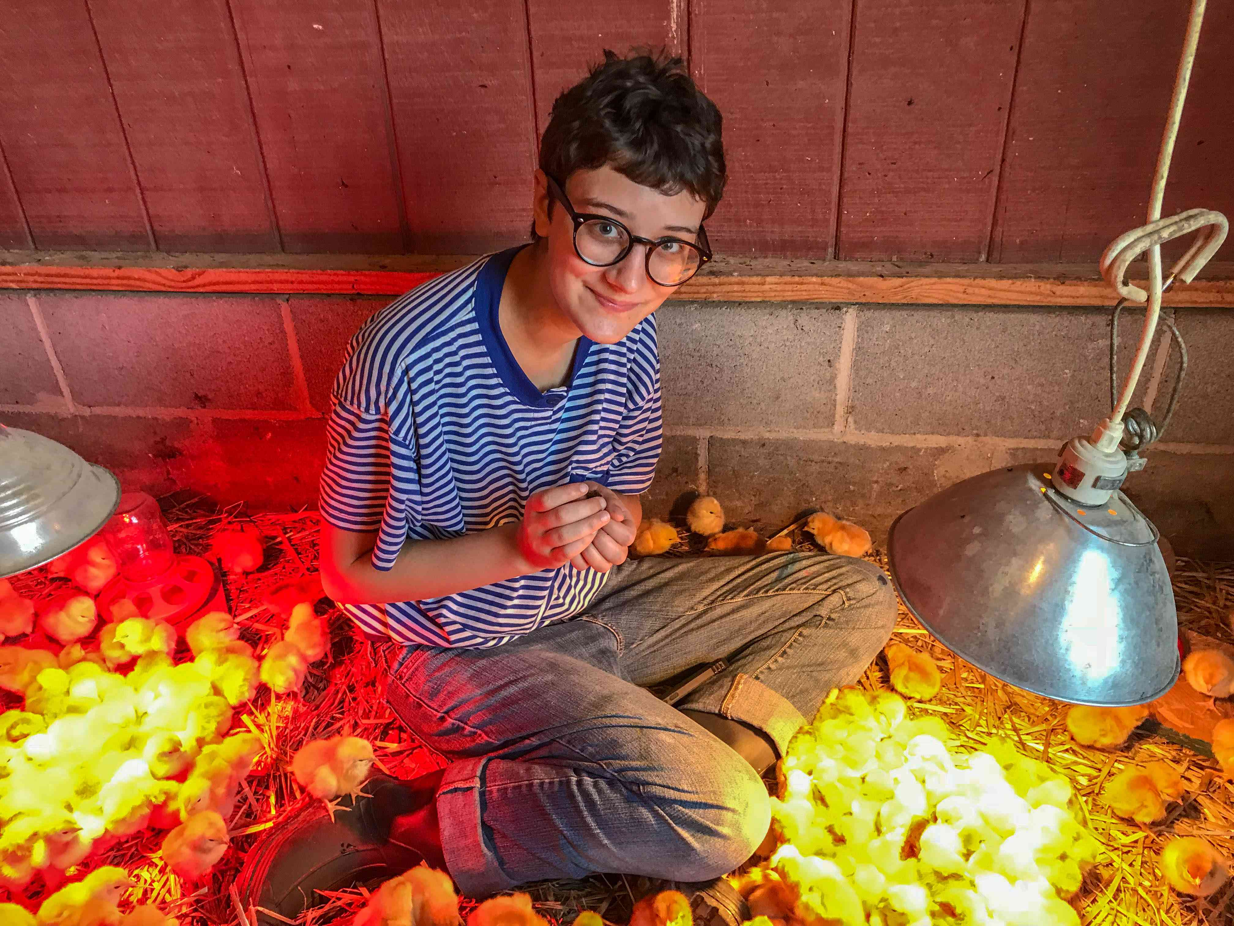 Student Noa Everet is surrounded by baby chicks.