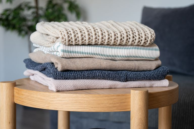stacks of folded clothes on wooden side table in living room