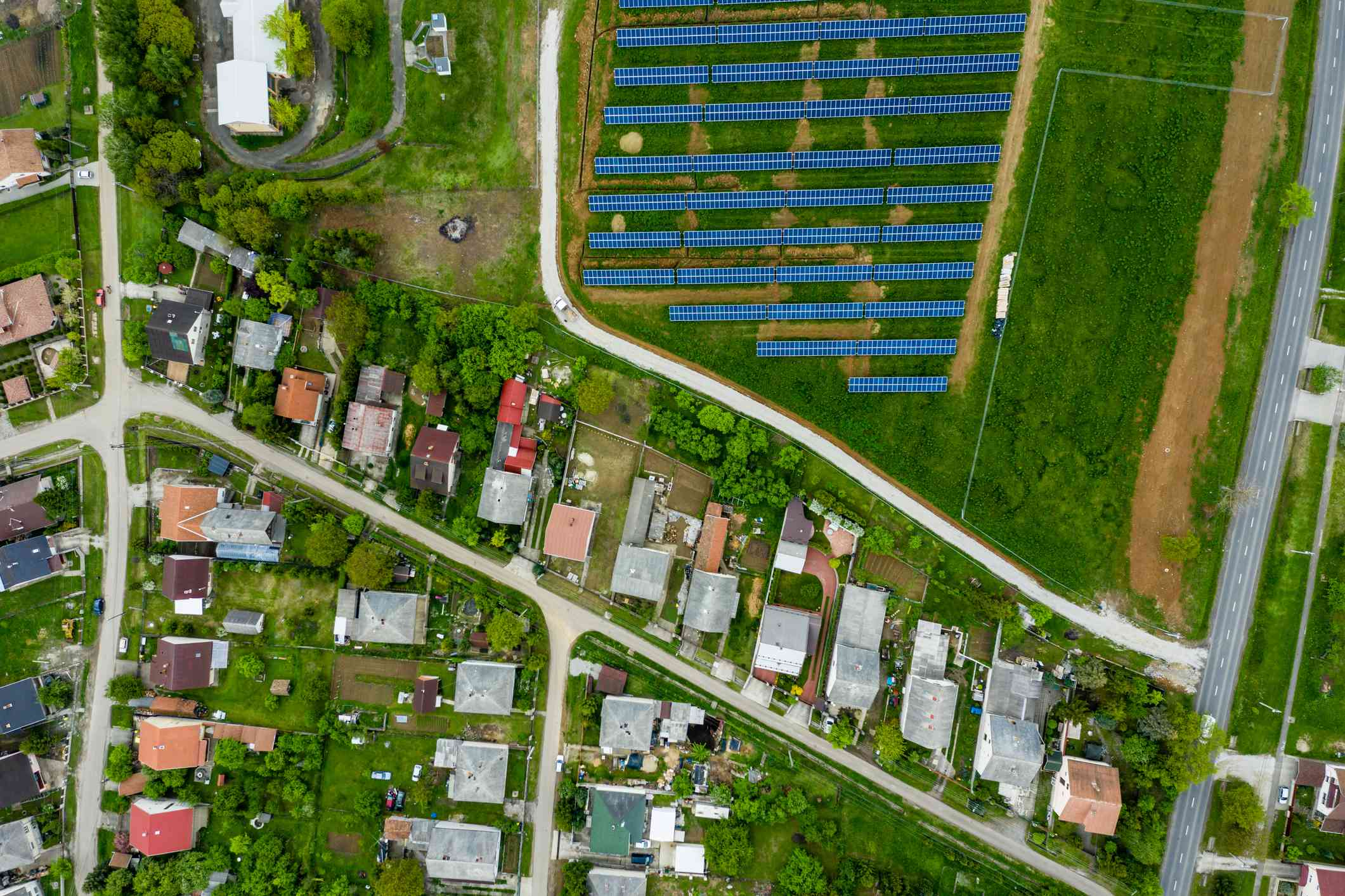 An aerial view shows a solar array in a field next to a residential neighborhood.