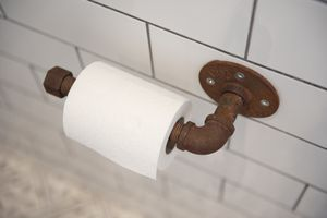 A roll of toilet paper on a rusty pipe holder.
