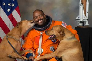 Leland Melvin poses with his dogs Jake and Scout in his 2009 NASA portrait