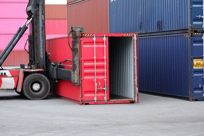 A machine lifting a red shipping container.