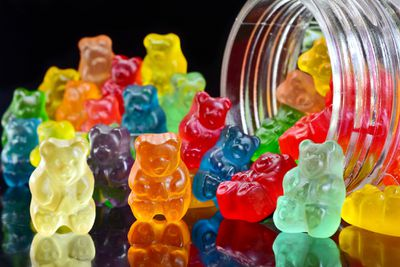 multi-colored gummy bears spilling out of a jar