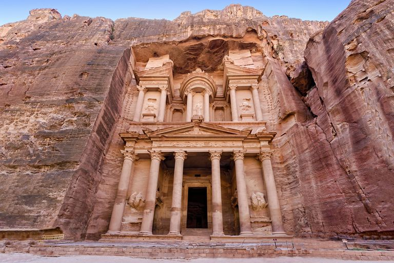 Front view of The Treasury or Al-Khazneh, an ancient structure carved into sandstone under a blue sky