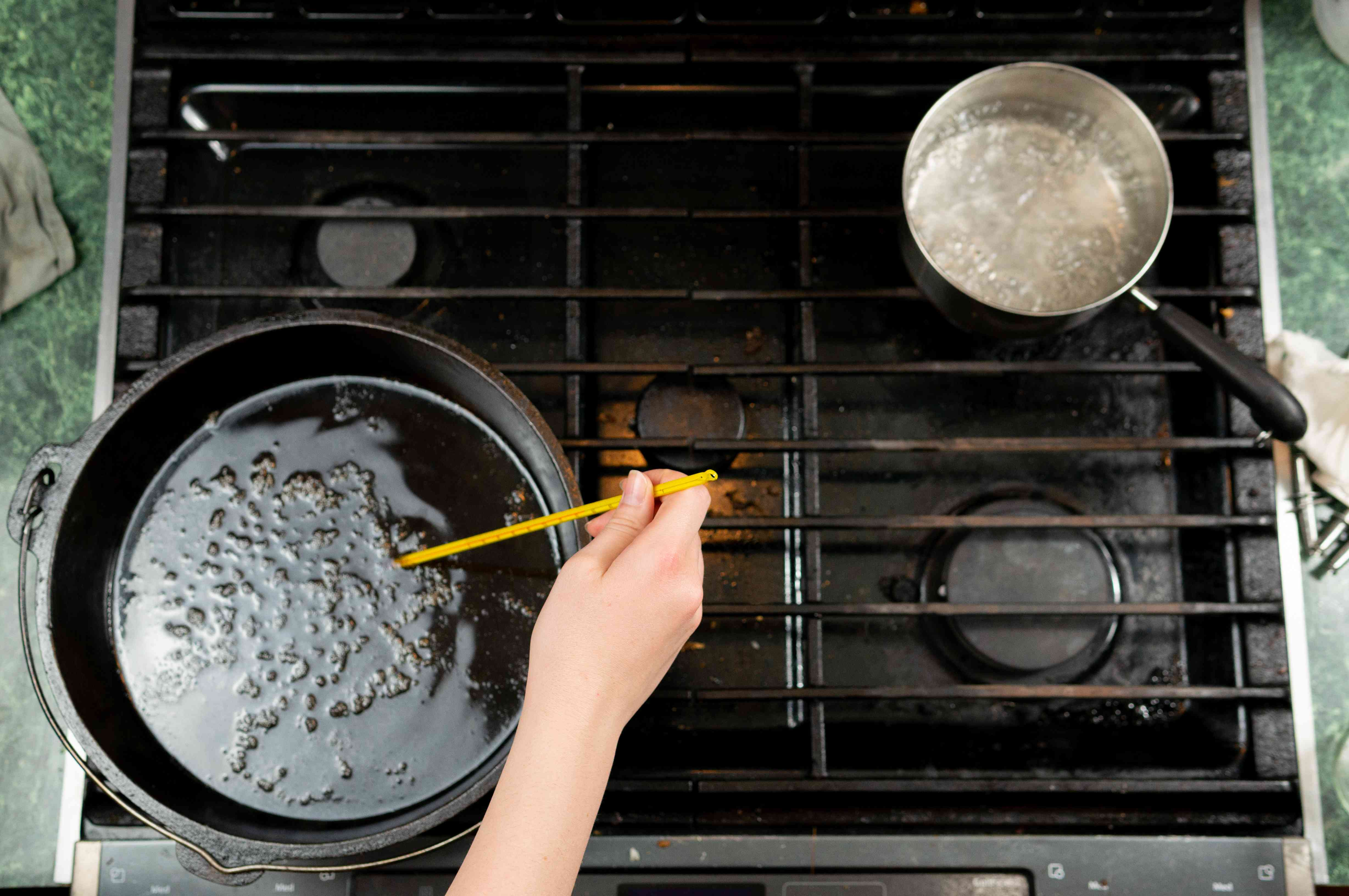testing boiling sugar on stove with thermometer