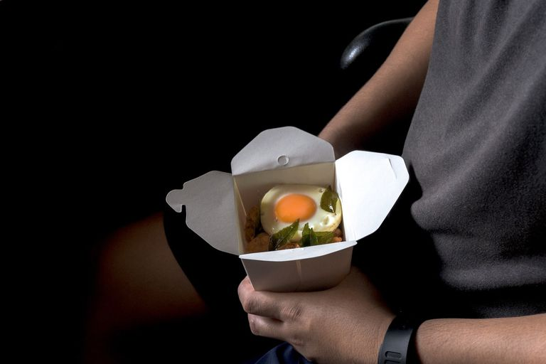person holding take out container