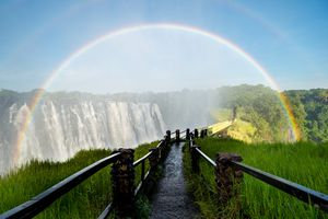 A rainbow hovers over a waterfall on a clear day.