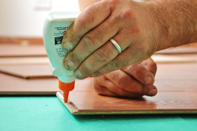 Man's hand wearing a wedding ring, applying glue to a piece of wood