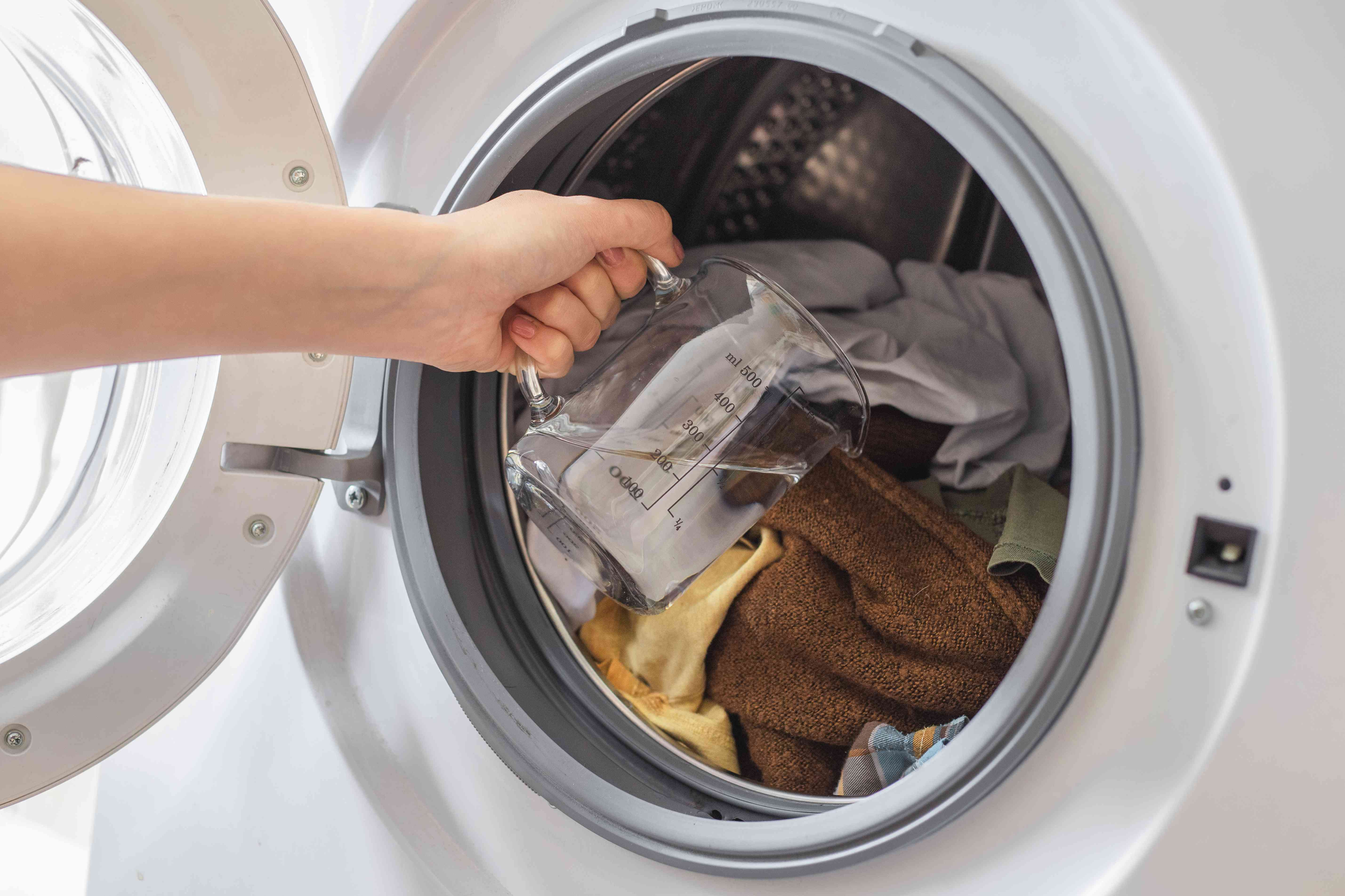 hand pours vinegar directly onto dirty clothes of open washing machine
