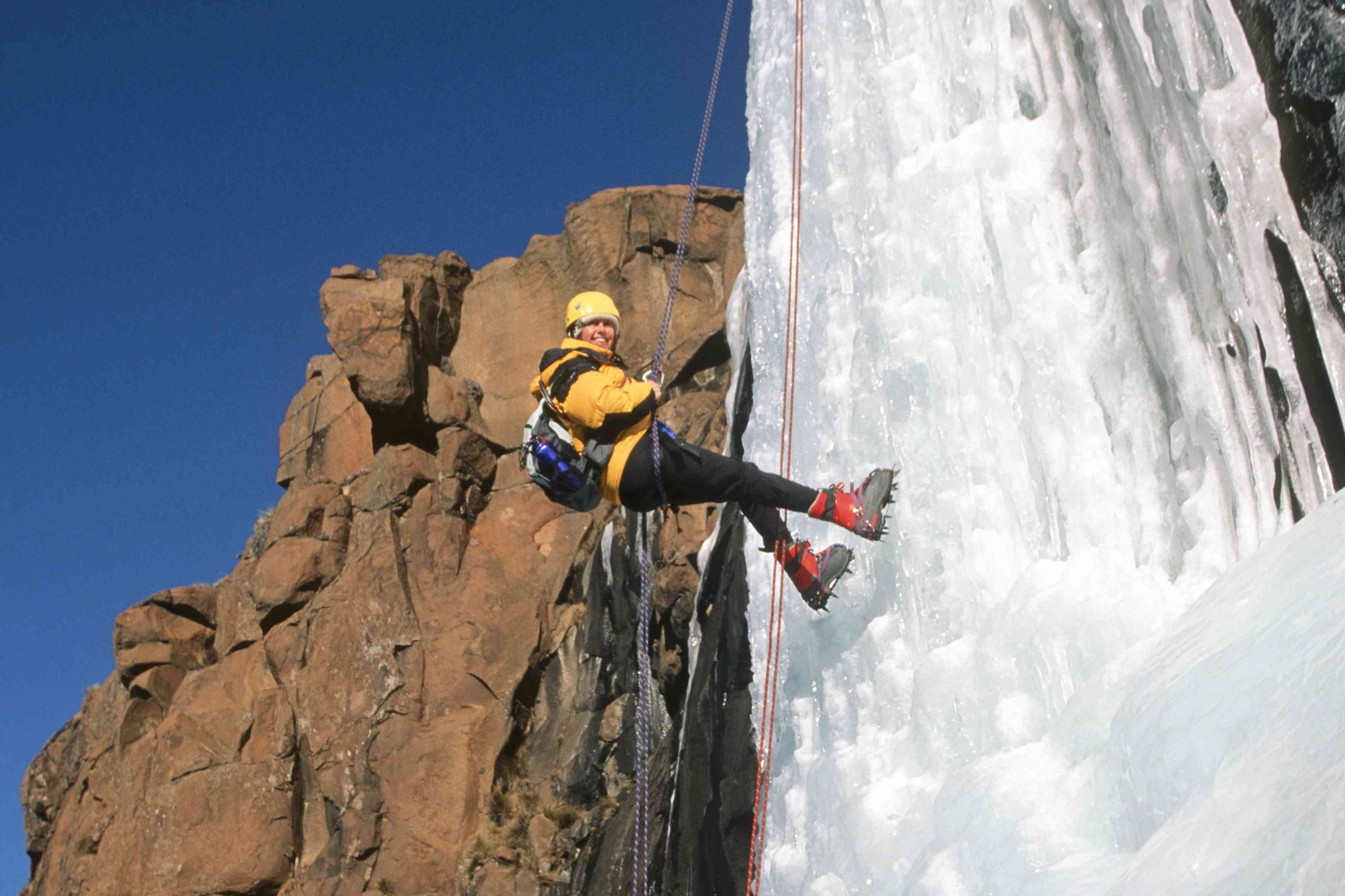 Smiling climber on frozen waterfall next to red rock formation