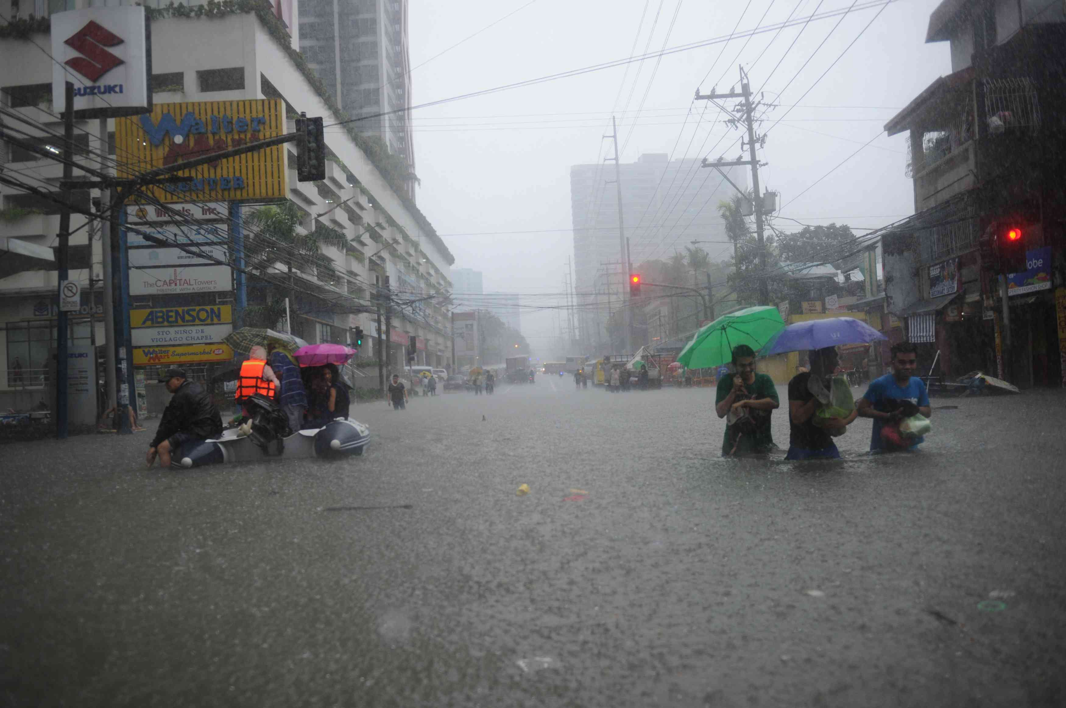 Manila residents attempting to make their way through a flooded street