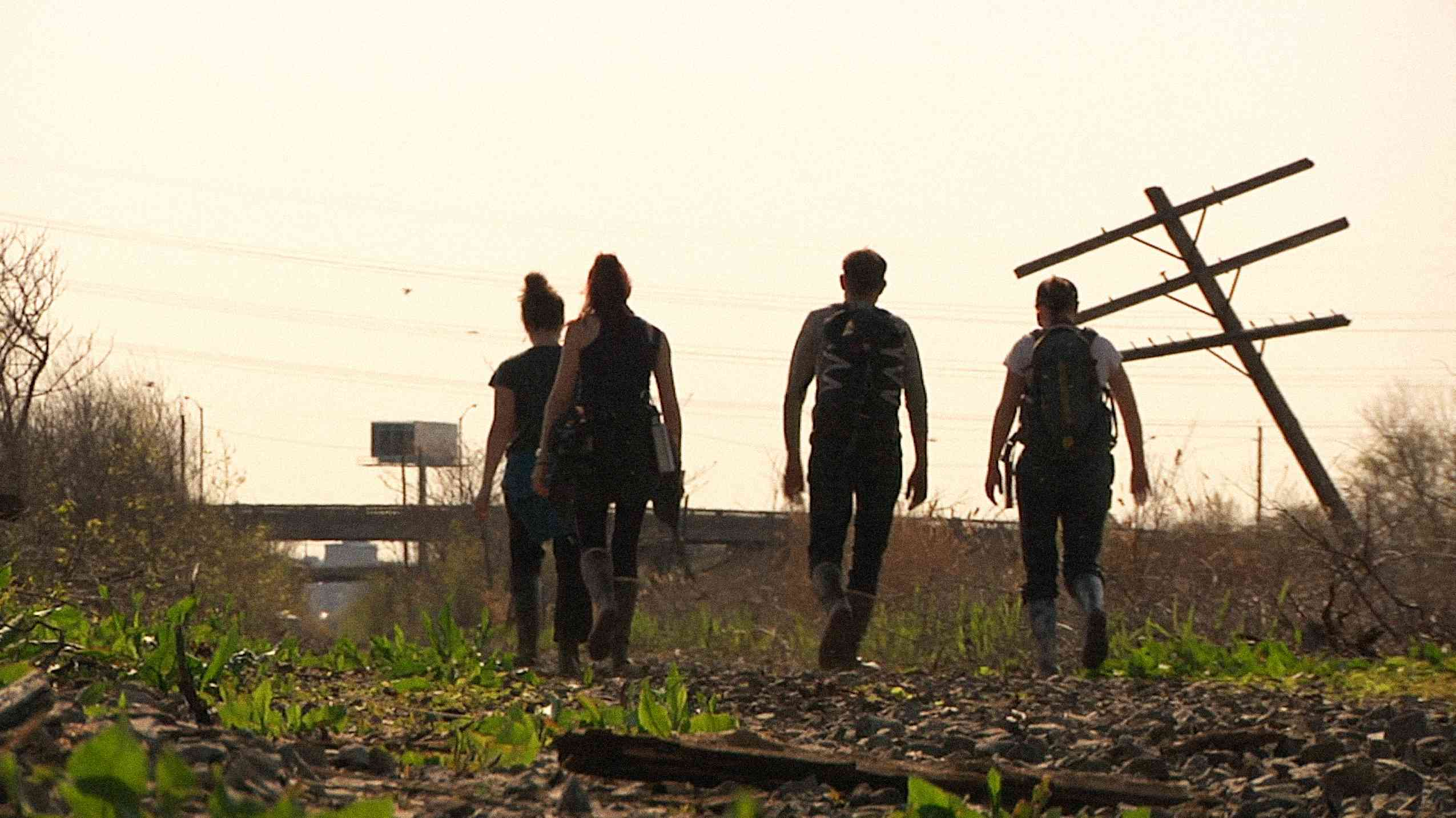Four members of the Back Water team walk into the light with their backs facing the viewer