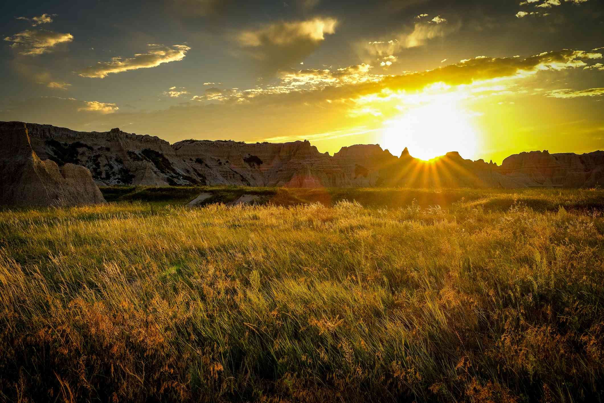 sunrise over Badlands National Park with mountains in the distance