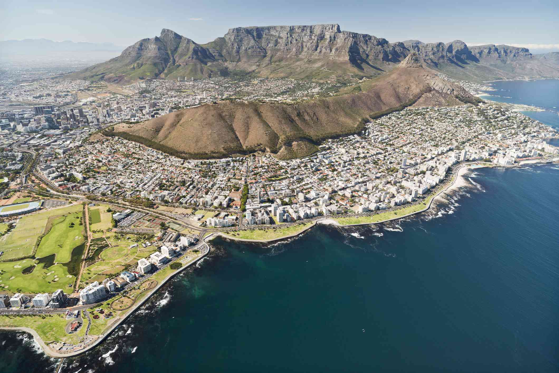 Aerial view of Cape Town, South Africa with view of Table Mountain in the distance and blue water in the foreground along the shoreline with light blue sky above
