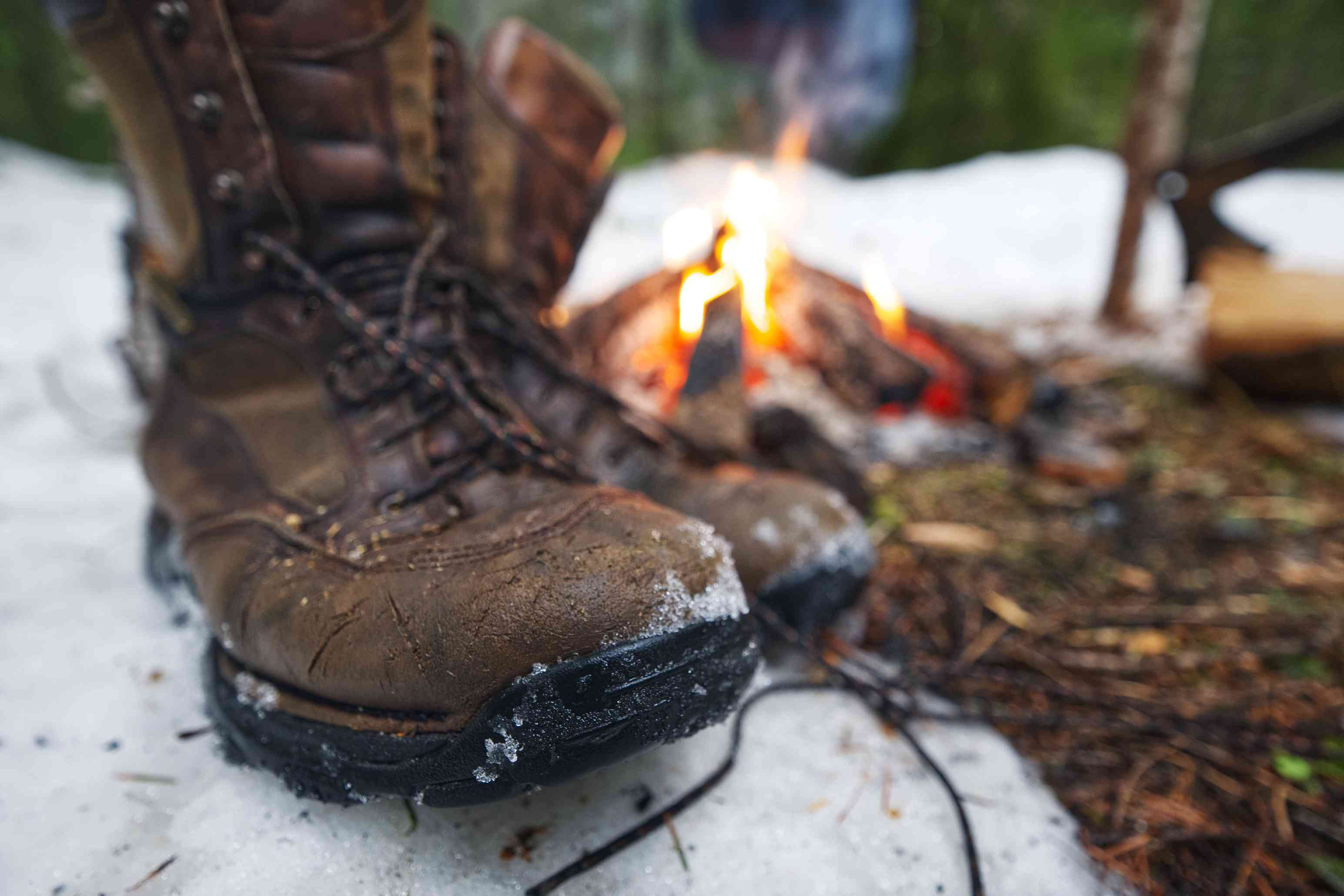 snowy boot next to campfire outside