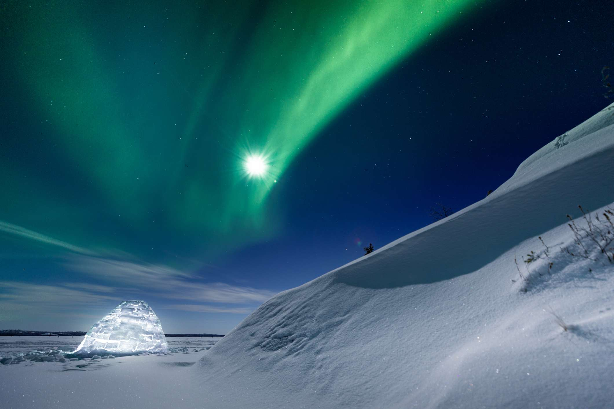 Glowing igloo and snow-covered landscape under the northern lights