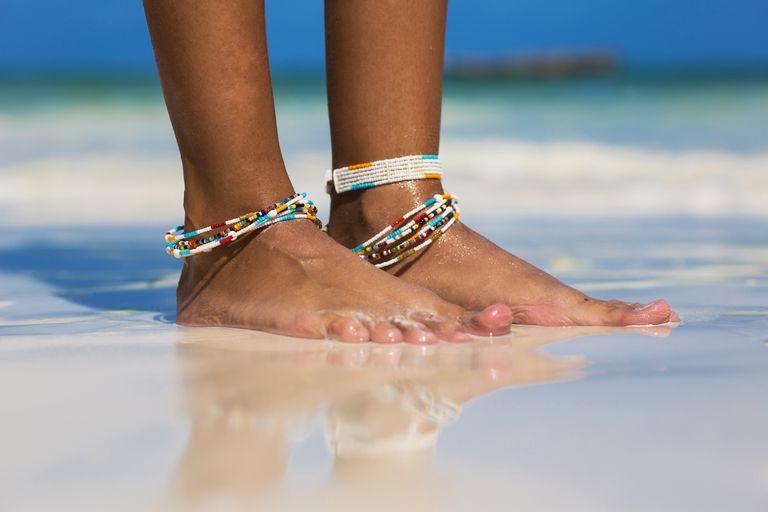 A black woman's feet with ankle bracelets on a sandy beach .