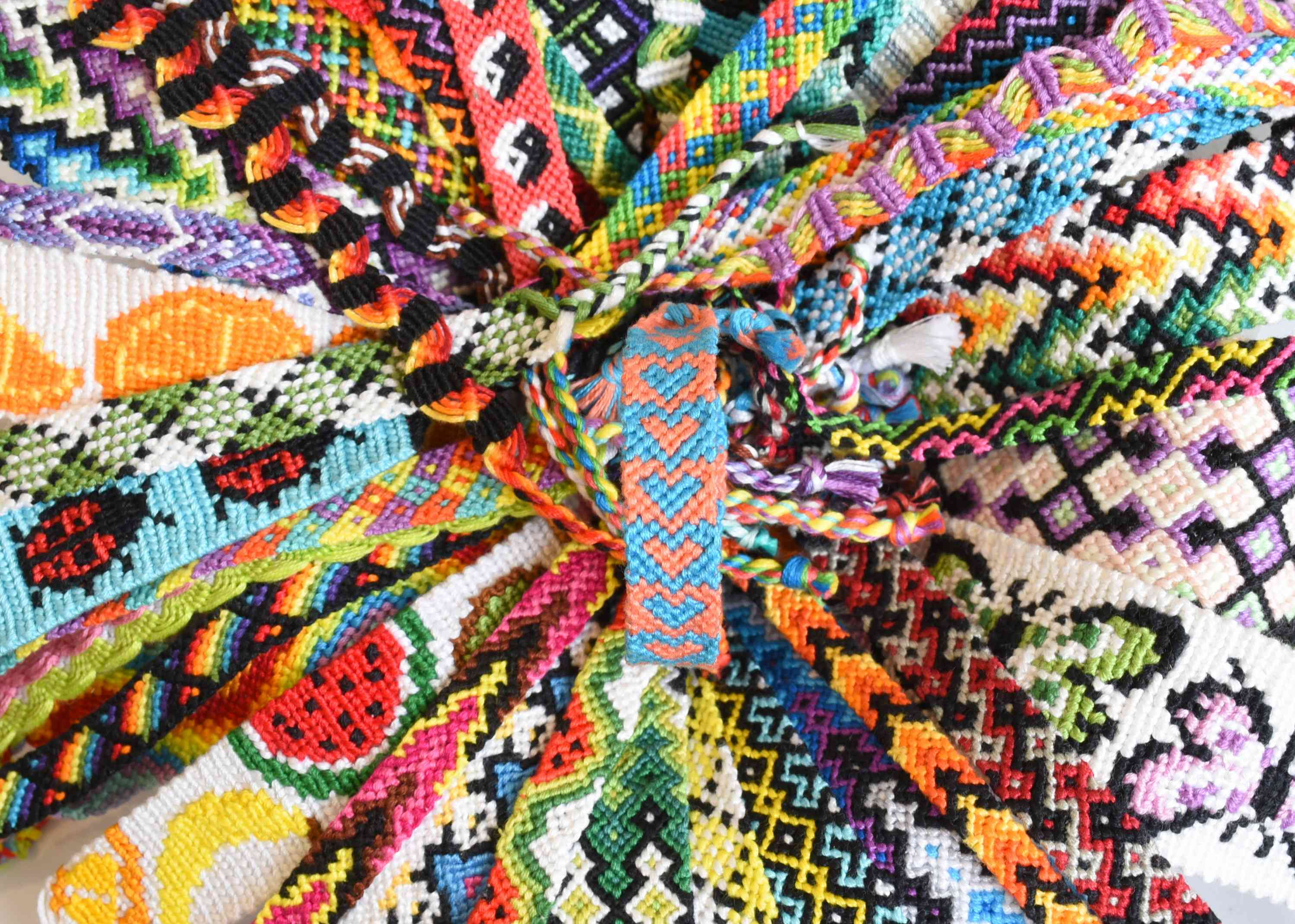 Pile of colorful friendship bracelets with different patterns