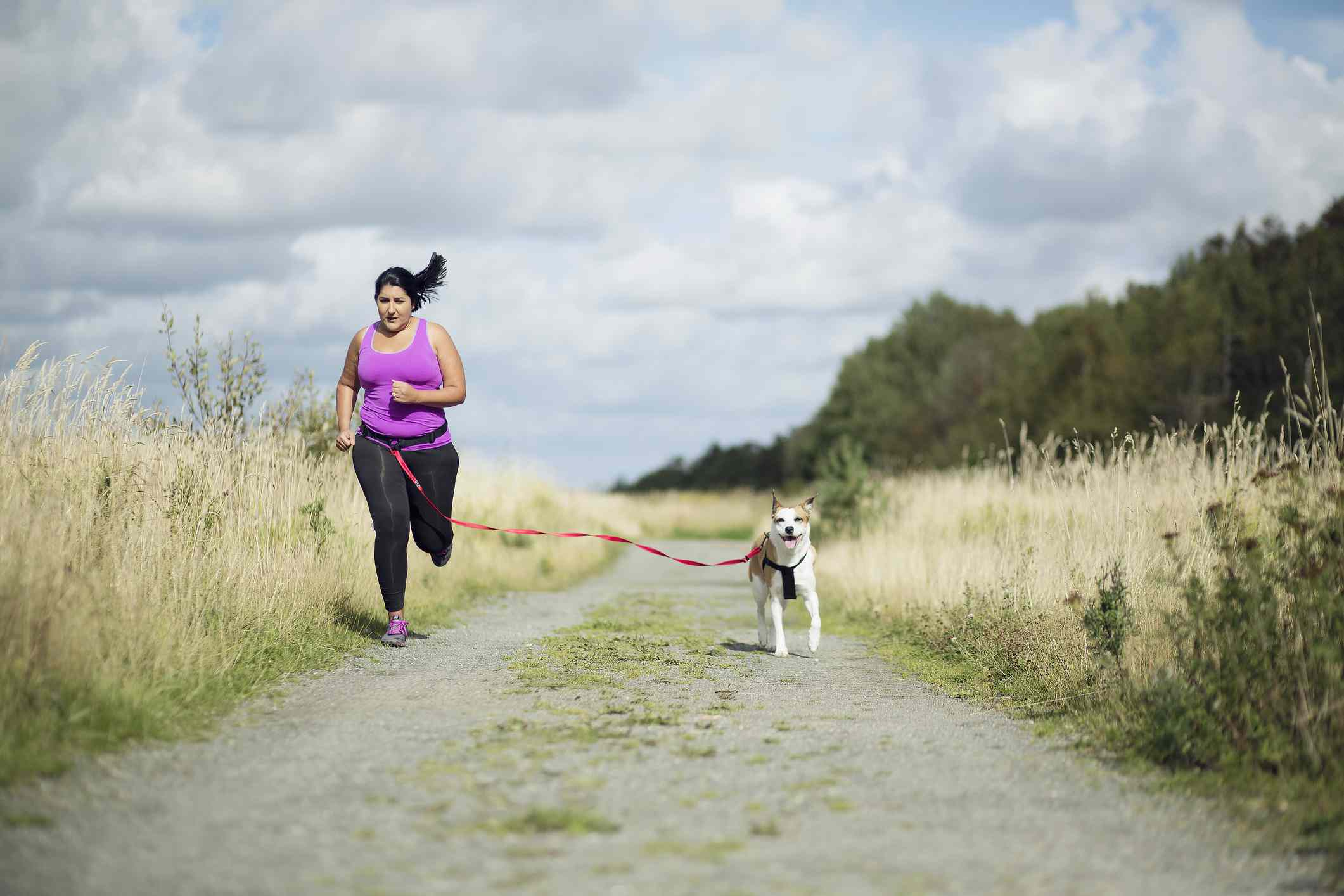 Female jogger running with dog on leash
